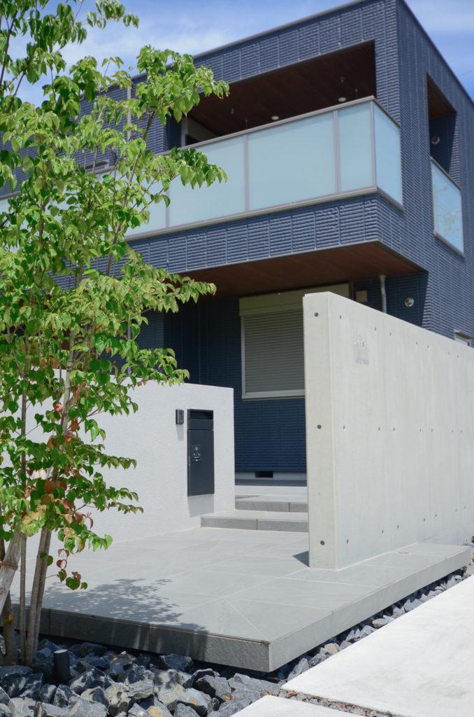 低い階段でゆったりと上がるアプローチ。道路側からは見えない奥の壁にインターホンとポストがある。